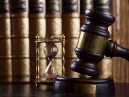 Gavel at the downward point of contact with hourglass and books in the background