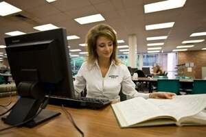 Woman working in front of a computer and simultaneously looking at a physical book on a table