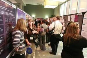 students and faculty viewing posters